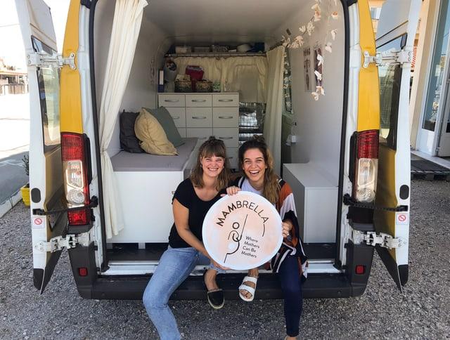 Die beiden Hebammen sitzen in der geöffneten Heckklappe des Lieferwagens, den sie mit zur bequemen und mobilen Beratungsstation für Mütter umgebaut haben.