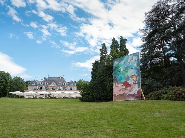 Eine riesige bemalte Leinwand steht in einem Park.