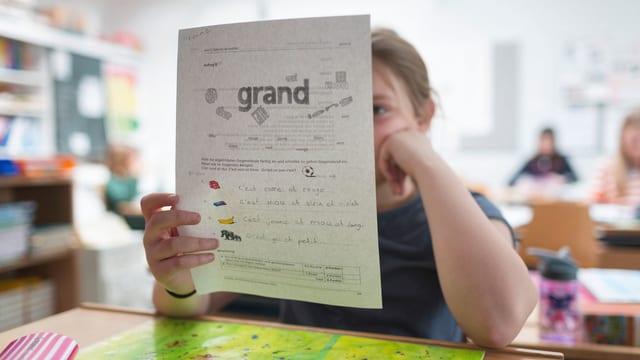 Ein Mädchen in der Schule hält sich ein Blatt vor den Kopf, auf dem das Wort «grand» zu lesen ist.