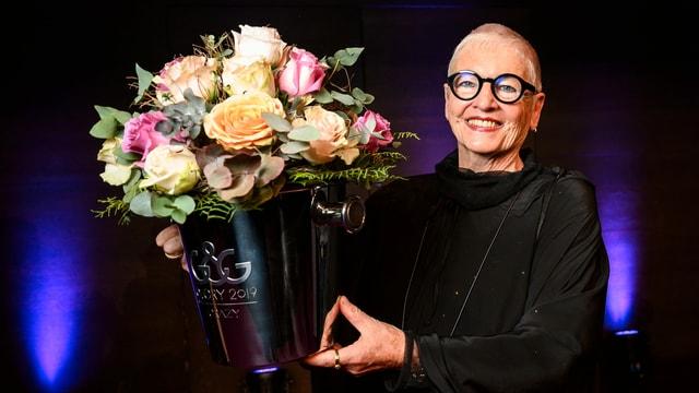 Frau in schwarzem Gewand mit Blumenstrauss in der rechten Hand