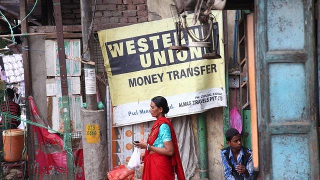 """Eine indische Frau läuft in Neu-Delhi an einem Schild vorbei, das Werbung macht für die Geldtransfer-Firma """"Western Union""""."""