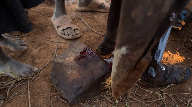 Blut auf einem Stein, eine Frau stehend darüber