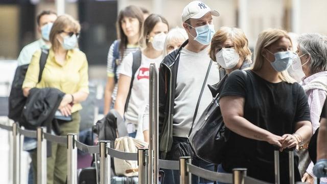Passagiere mit Schutzmasken am Flughafen Zürich.
