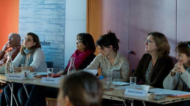 Die Jury, bestehend aus 6 Personen, an einem langen Tisch sitzend, zuhörend, Notizen machend.