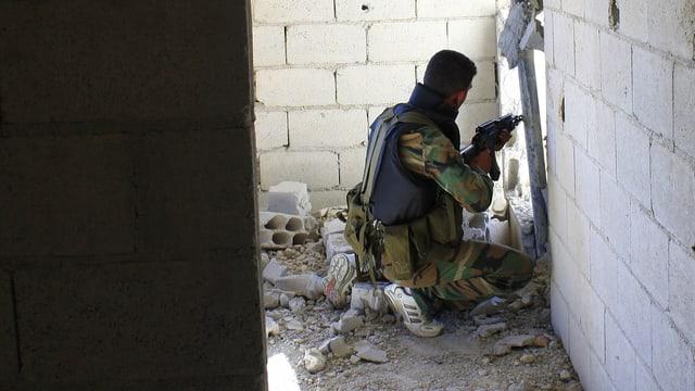Ein Rebellen-Soldat kniet in der Ecke eines Gebäudes und schiesst durch ein Loch in der Mauer.