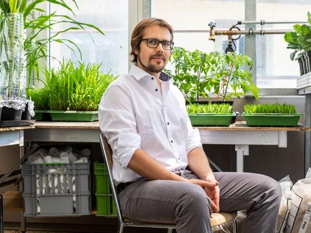Matthias Erb in weissem Hemd sitzt im Labor vor seinen Pflanzen