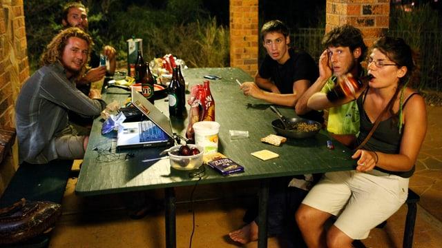 Junge Leute sitzen zusammen um einem Tisch, darauf ein Computer und Getränke.