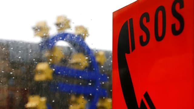 Im Bildvordergrund ist eine SOS-Tafel zu sehen. Dahinter, etwas unscharf, das Euro-Emblem.