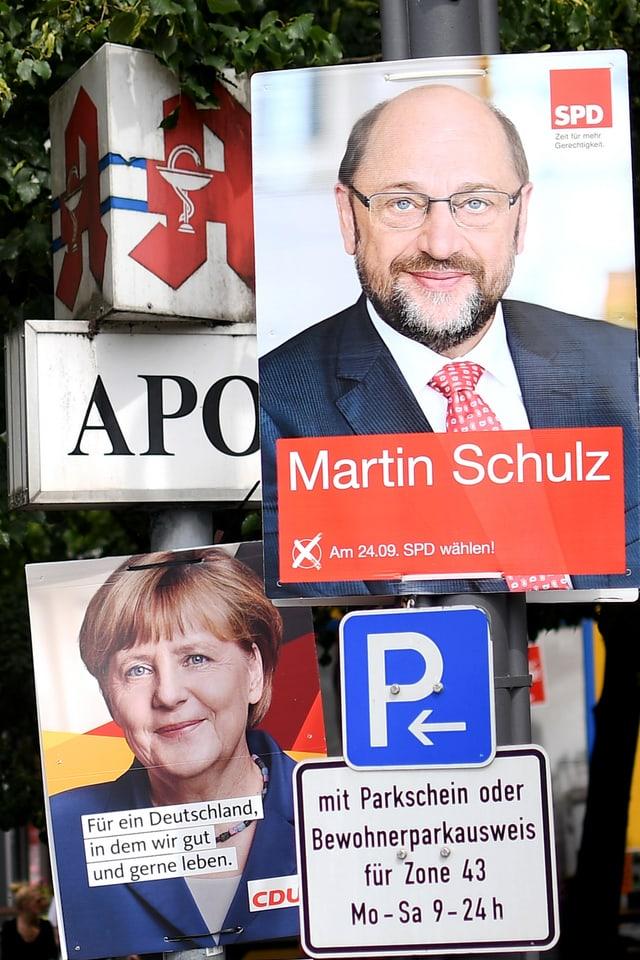 Placats dad Angela Merkel e Martin Schulz vid in pitga cun tavla da parcar ed inscripziuns.