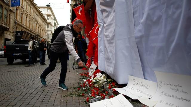 Ein Mann legt am Ort des Anschlages rote Rosen nieder.