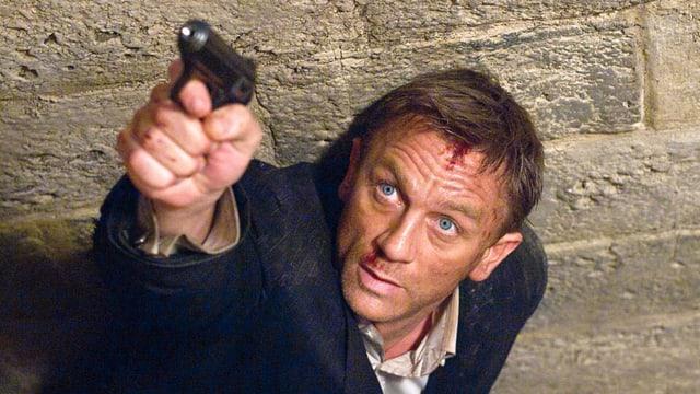 Der Charakter James Bond zielt mit einer Waffe.