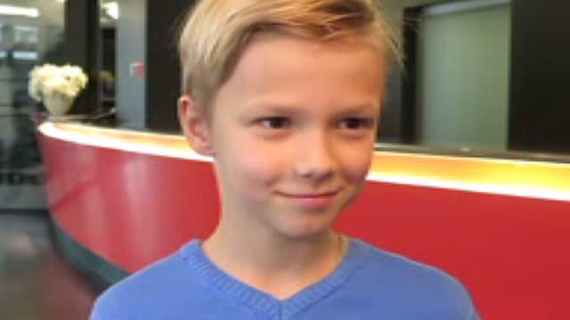Ein blonder Junge in einem blauen Pulli