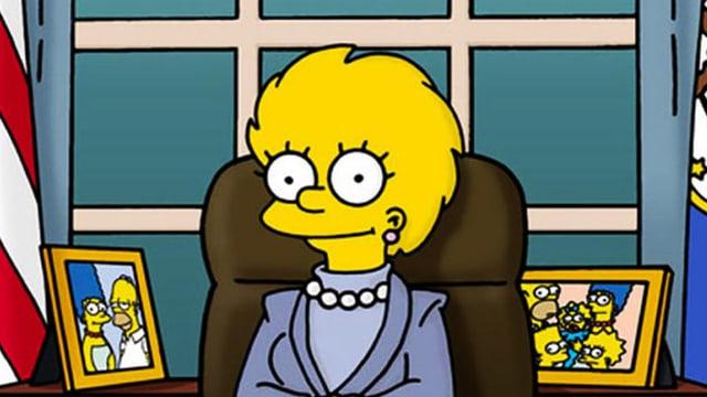 Lisa Simpson sitzt an einem Schreibtisch, neben ihr steht die US-amerikanische Flagge.
