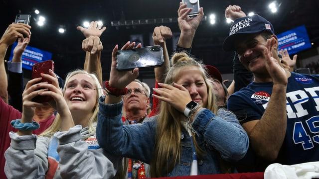 Fans von Donald Trump halten Handys hoch, eine junge Frau wischt sich Tränen ab.