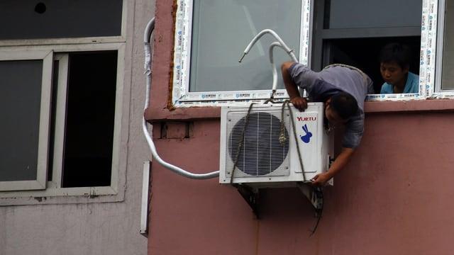 Ein Mann montiert ein Klimagerät unter einem Fenster.