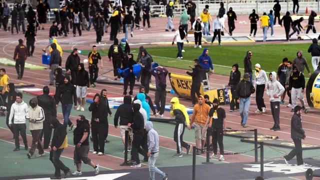 Athener Ultras stürmen das Spielfeld.