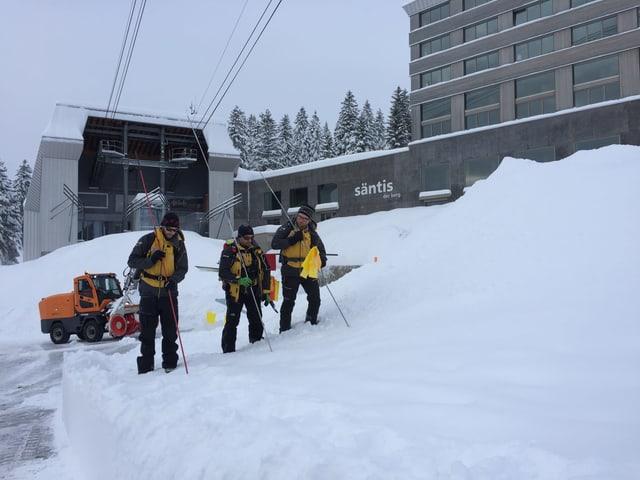 Drei Retter suchen den Schnee ab
