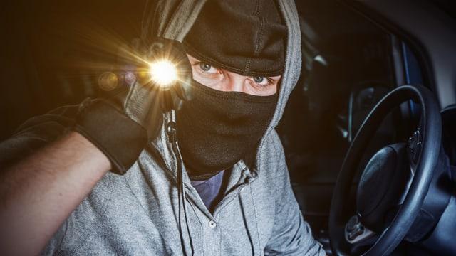 Ein vermummter Mann leutet mit einer Lampe in die Kamera