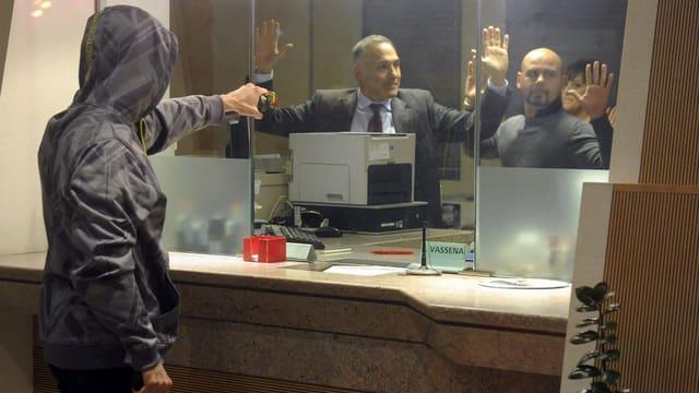 Ein Mann mit Kapuze überfällt eine Bank. Es ist jedoch nur eine Übung.