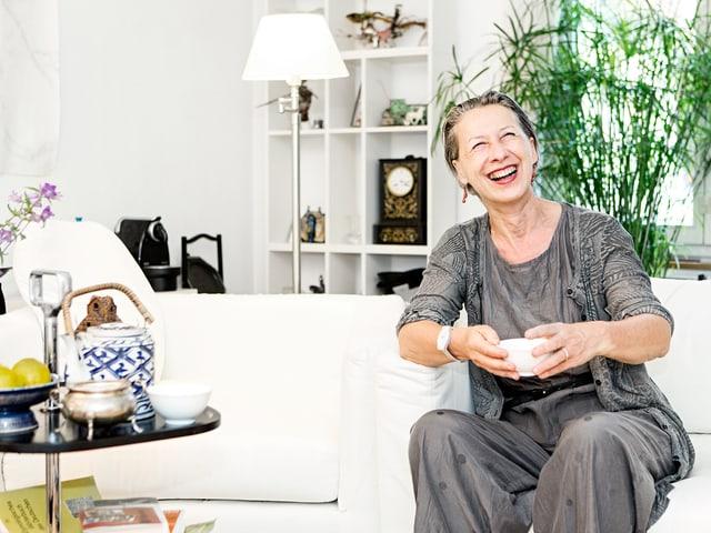 Anne-Dominique Hubert auf ihrem Sofa in der Wohnung. Sie trinkt aus einer Tasse.