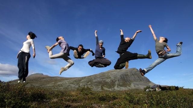 Sechs Tänzerinnen und Tänzer springen in freier Natur in einer markanten Pose in die Luft.