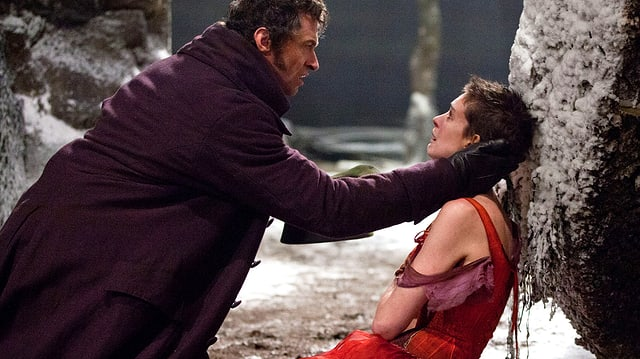 Schauspieler Hugh Jackman hält seine Hände um den Hals von Anne Hathaway, die eine Prostituierte spielt.