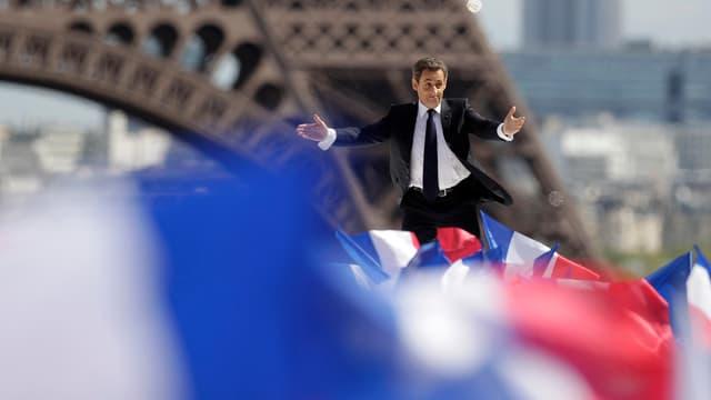 Nicolas Sarkozy scheinbar auf einem Fahnenmeer stehend vor dem Eifelturm.