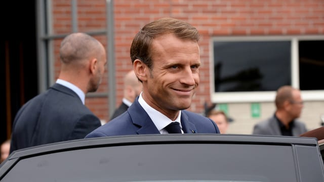 Emmanuel Macron steigt in ein Auto ein.