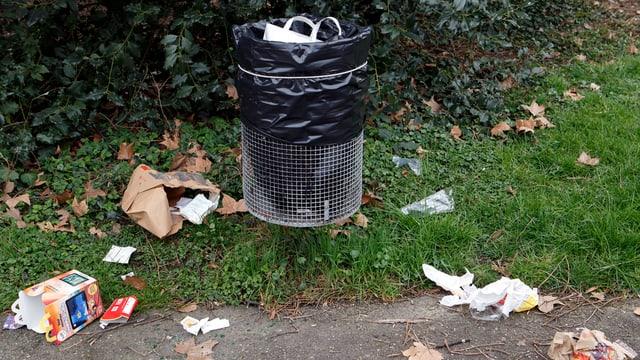 Abfall liegt um einen öffentlichen Abfalleimer herum.