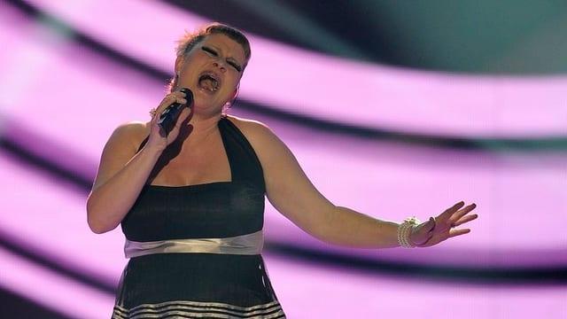 Nicole Bernegger singend am Samstag Abend vor violettem Hintergrund.