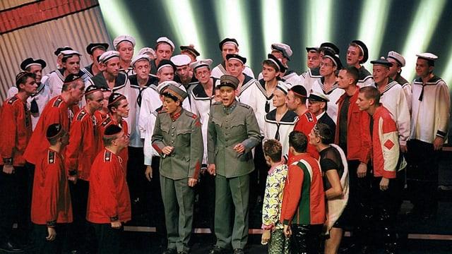 Männer in Matrosenkleidung stehen in einem Halbkreis auf einer Bühne.