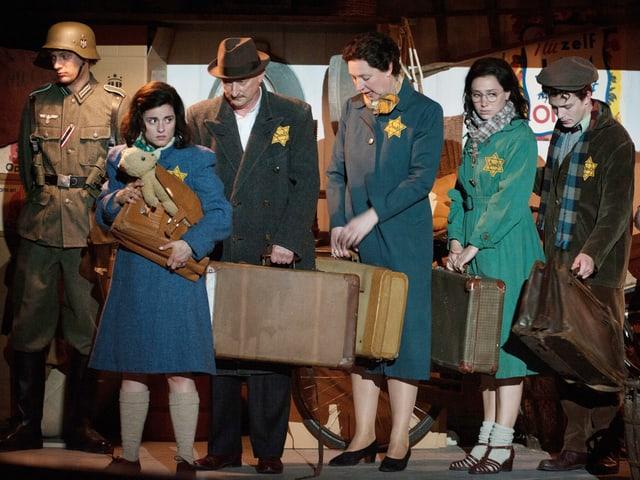 Anne Frank trägt eine Tasche und einen Teddy und wartet zusammen mit anderen Juden.