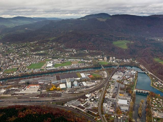 Flugaufnahme: Bahngeleise, Stadt, Fluss und im Hintergrund ein Berg
