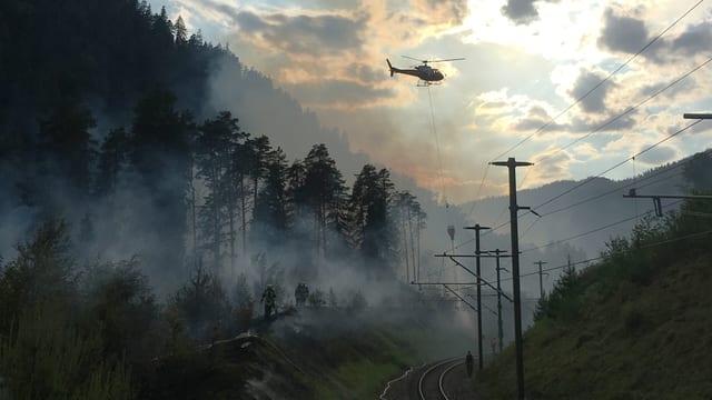 Ein Helikopter in Abenddämmerung am Löschen