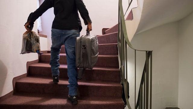 Ein Flüchtling trägt seine Koffer die Treppe hoch.