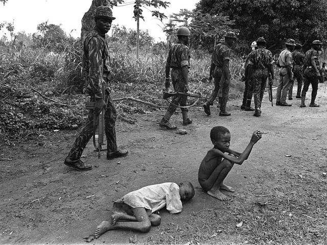 Soldaten der nigerianischen Bundesarmee gehen an zwei abgemagerten Kindern vorbei.