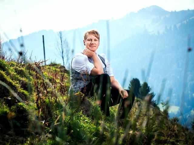 Astrid sitzt in einer Wiese, im Hintergrund sind grüne Hügel zu sehen.