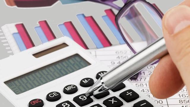 Ein Mann tippt mit einem Kugelschreiber Zahlen in einen Taschenrechner. Dahinter liegen ein Balkendiagramm und eine Brille.
