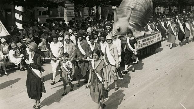 eine schwarz-weiss Fotografie von demonstrierenden Frauen, die eine grosse Schnecke ziehen