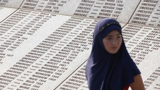 Ein Mädchen mit Kopftuch steht vor einer Tafel mit den Namen der Opfer von Srebrenica.
