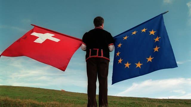 Mann hält je Schweizer- und EU-Flagge