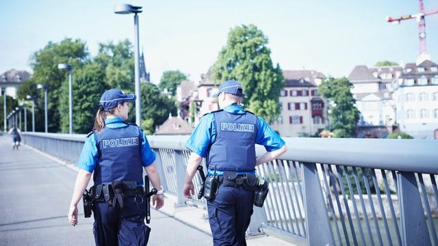 Eine Polizistin und ein Polizist der Basler Kantonspolizei gehen über die Wettsteinbrücke. Man sieht die beiden von hinten.