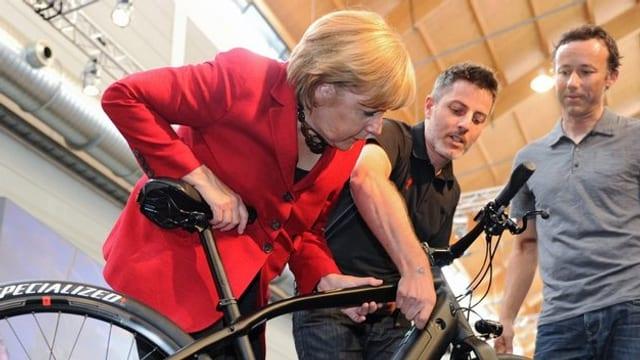 Angela Merkel im roten Blazer beugt sich über ein schwarzes Mountainbike. Zwei Männer erklären ihr im Hintergrund etwas.