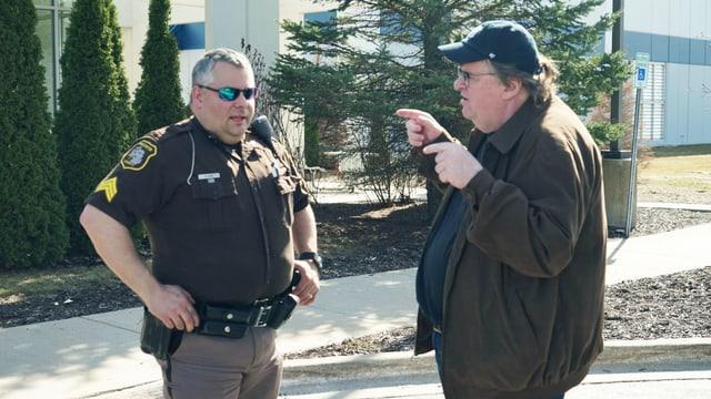 Regisseur Michael Moore spricht mit einem Polizisten.
