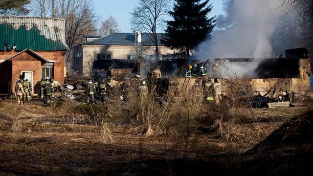 Feuerwehrmänner in den qualmenden Trümmern der abgebrannten Klinik