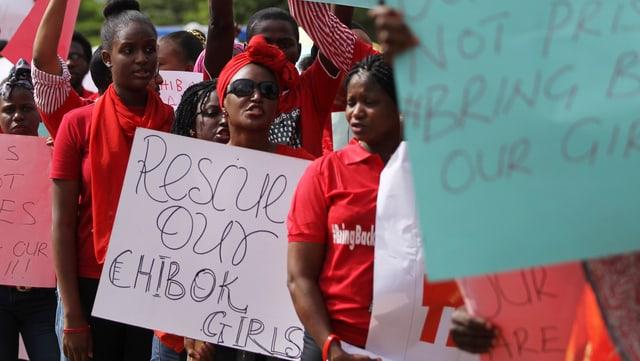 Demoteilnehmer in Abuja mit roten T-Shirts und Schildern, auf denen steht, rettet unsere Chibok-Mädchen.