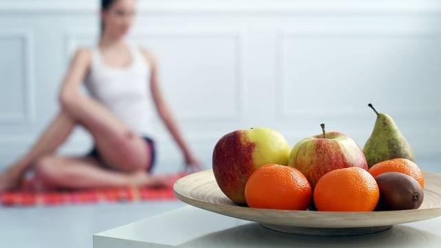 Früchteschale, hinter der eine Frau eine Yoga-Übung macht.