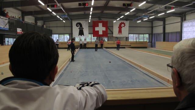 In einer Halle spielen zwei Mannschaften Boccia, im Hintergrund sind die Fahnen der Schweiz und der Kantone Baselland und Basel - Stadt.