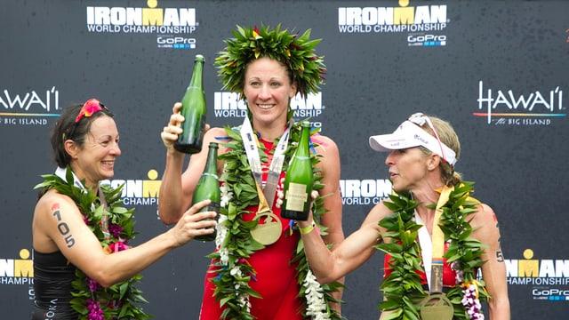 Daniela Ryf mit Blumenkranz auf Kopf und Flasche in der Hand auf dem Siegerpodest