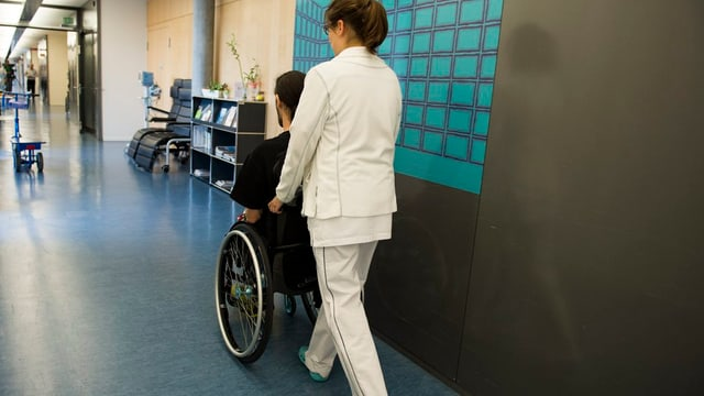 Krankenschwester schiebt Patienten im Rollstuhl durch einen Gang